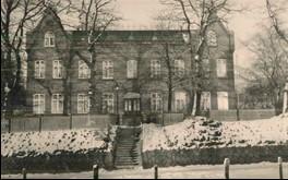 Vorderseite der Alten Verwaltung; es liegt Schnee. Links und rechts ist ein Hang zu sehen, an dessen oberen Enden steht ein hoher Zaun. Dazwischen führen Treppenstufen hoch zu einer dunklen Eingangstür. Vor dem Backsteingebäude stehen kahle Bäume.