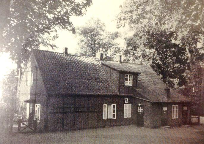 Zu sehen ist hier die Vorderseite des Fachwerkhauses. Rechts ein kleiner Vorsprung, mit drei Türen, aus dessen geziegeltem Dach ragt ein Schornstein hinaus. Links ist eine kleine Pforte zu sehen, die zu einer weiteren Haustür führt. Im Hintergrund stehen Bäume.