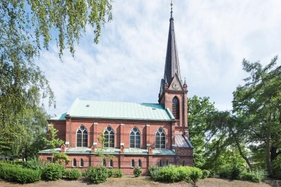 Die aus roten Backsteinen erbaute St. Nicolaus-Kirche besteht aus einer Saalkirche und einem Kirchturm, im Bild hier rechts zu sehen. Das hohe, spitz-zulaufende sogenannte Helmdach des Turms ist grau, ein goldenes Kreuz bildet die Dachspitze. Das Dach der Saalkirche ist grün. Die Saalkirche hat vier große, nebeneinander angeordnete Fenster, darunter kommt ein kleiner Vorsprung mit acht weiteren, kleineren Fenstern. Am Kirchturm befindet sich eine Uhr mit grauem Ziffernblatt und goldenen Zeigern, darunter gibt ein langes, offenes Fenster Sicht auf die Kirchenglocken.