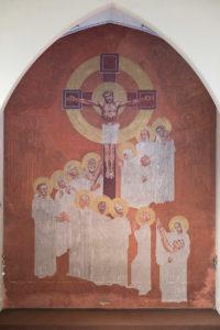 Altarbild von 1938; im Mittelpunkt der gekreuzigte Jesus. Das Kreuz ist von einem Heiligenschein umgeben, ebenso Jesus Christus. Zu seinen Füßen stehen 15 Menschen in einer Reihe; diese beginnt schräg rechts hinter dem Kreuz, geht links herum und endet rechts unten. Alle tragen weiße Gewänder; zwölf von ihnen einen Heiligenschein, drei nicht.