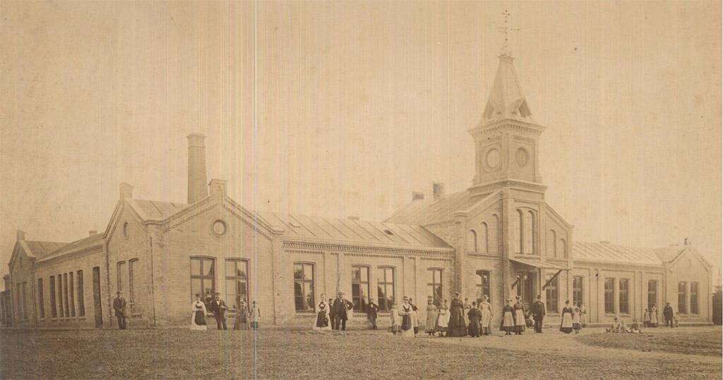 Zu sehen sind die Vorderseite und die linke Längsseite des Herntrich-Hauses. Ausgehend vom rechten Bildrand führt ein Weg hin zum Eingang. Mehrere Personen sind zu sehen. Auf dem Dach des Eingangs sitzt ein kleiner Turm.