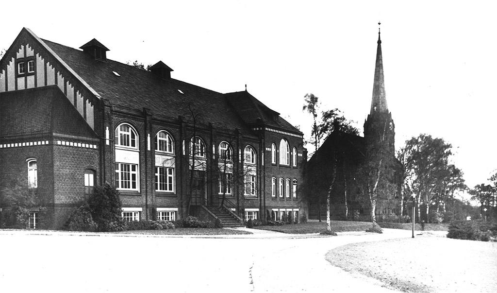 Von vorne führt ein breiter Weg in Richtung Studienhaus und Kirche St. Nicolaus, deren Kirchturm im Hintergrund zu sehen ist. Das Haus wurde schräg von vorne fotografiert, die Hälfte der linken Giebelseite ist zu erkennen. Es gibt große, abgerundete Fenster, eine Treppe führt hinauf zum Eingang.