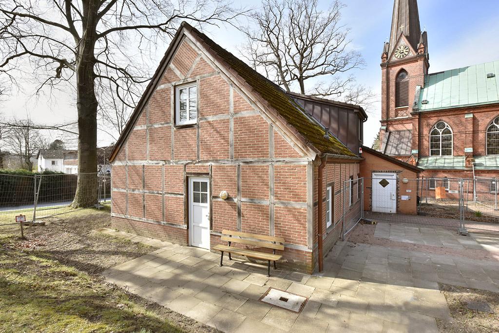 Giebelseite des Hauses Schönbrunn, davor eine Bank. Hier gibt es eine kleine Tür, darüber ein Fenster. Um das kleine Fachwerkhaus herum stehen Bauzäune, links im Bild ist ein Baum zu sehen. Rechts im Hintergrund ist die Kirche St. Nicolaus zu sehen.