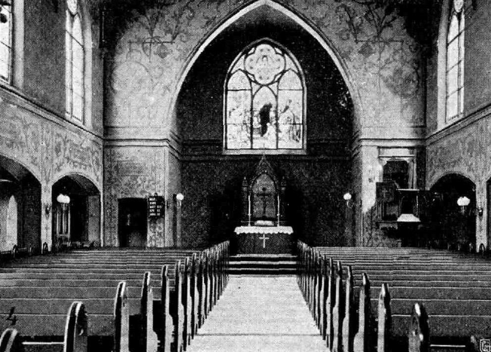 Die Kirche St. Nicolaus von innen; Blick in Richtung Altar. Rechts und links Kirchenbänke. Am Altar ist ein kleines Kreuz angebracht, obendrauf steht ein weiteres Kreuz, davor liegt die Bibel. Daneben stehen zwei Kerzen. Über dem Altar ist hinten in der Kirchenwand das alte Fensterbild zu sehen.