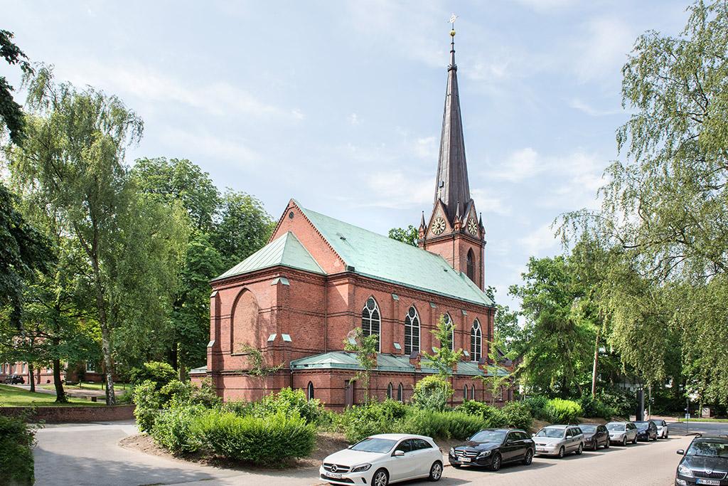 Rückansicht Kirche St. Nicolaus; im Vordergrund stehen Autos am Straßenrand. Vorne links eine Auffahrt zur Kirche. Rechts, links und um die Kirche drumherum stehen grüne Bäume und Büsche. Das historische Gebäude wurde aus roten Backsteinen erbaut, das Dach ist türkis. Ein Teil des Kirchturms und dessen grauen Dachs ist zu sehen.