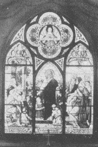 Bemaltes Kirchenfenster; zu sehen ist Jesus Christus mit einem Heiligenschein. Er segnet ein Kind, das links vor ihm kniet und zu ihm aufschaut. Zwei weitere Kinder knien vor ihm nieder, links und rechts stehen mehrere Menschen. Oben im Fenster sieht man einen Engel, rundherum Blumen.