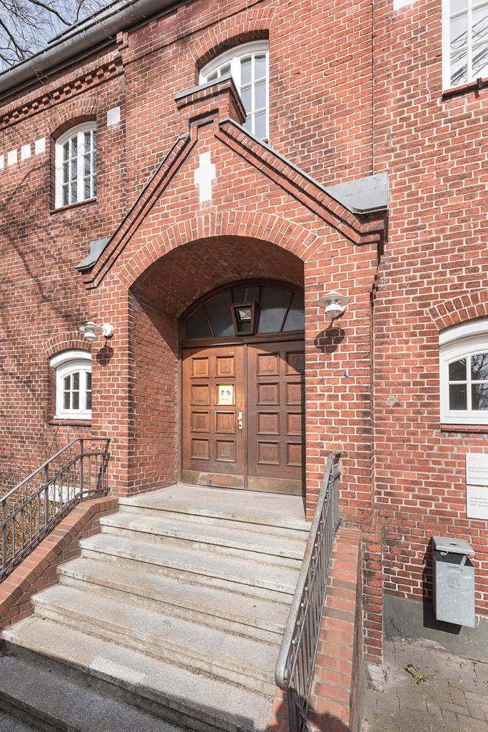 Sieben Stufen führen hinauf zur Eingangstür des Studienhauses. Die dunkle Doppeltür ist überdacht und von roten Mauern umgeben. Links und rechts hängt je eine Wandlampe und oben, am Giebel über der Tür wurde ein weißes Kreuz aufgemalt.