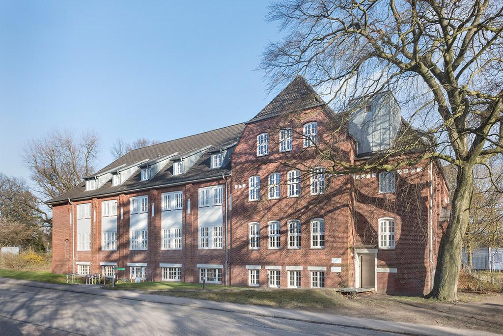 Rückansicht des Studienhauses; rechts im Bild steht ein Baum ohne Blätter. Links daneben führt ein Steg zum Hintereingang, die weiße Tür ist halb geöffnet. Das Haus hat eine Backsteinfassade, das Dach ist grau geziegelt. Rechts auf dem Dach ein hellgrauer Anbau.