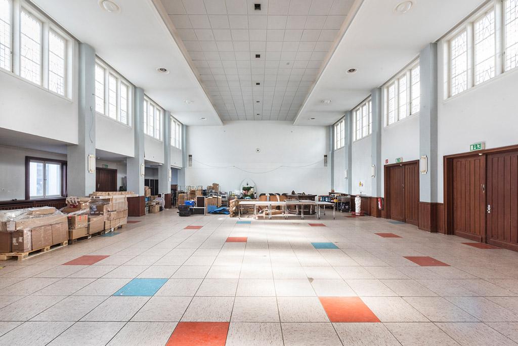 Ein langer, hell gefliester Saal; im Hintergrund und auf der linken Seite stehen Stühle, Tische und Kartons auf Paletten. Rechts befinden zwei große, dunkle Holztüren. Rechts und links gibt es oben an den Wänden Fenster, die bis zur Decke gehen.
