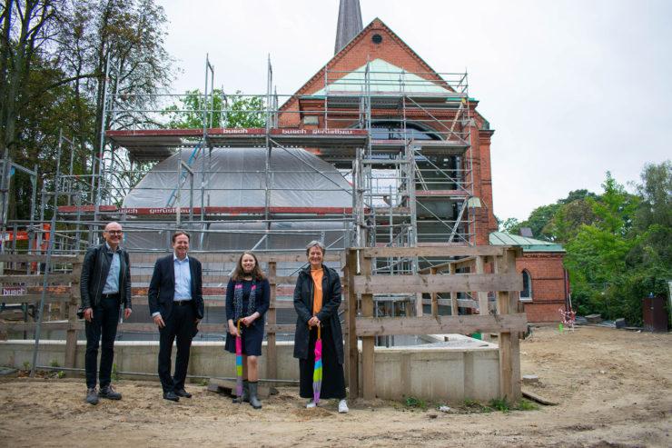 Axel Philipp Loitzenbauer, Ulrich Scheibel, Dr. Melanie Leonhard und Hanne Stiefvater vor dem Lern- Und Gedenkort und der Kirche